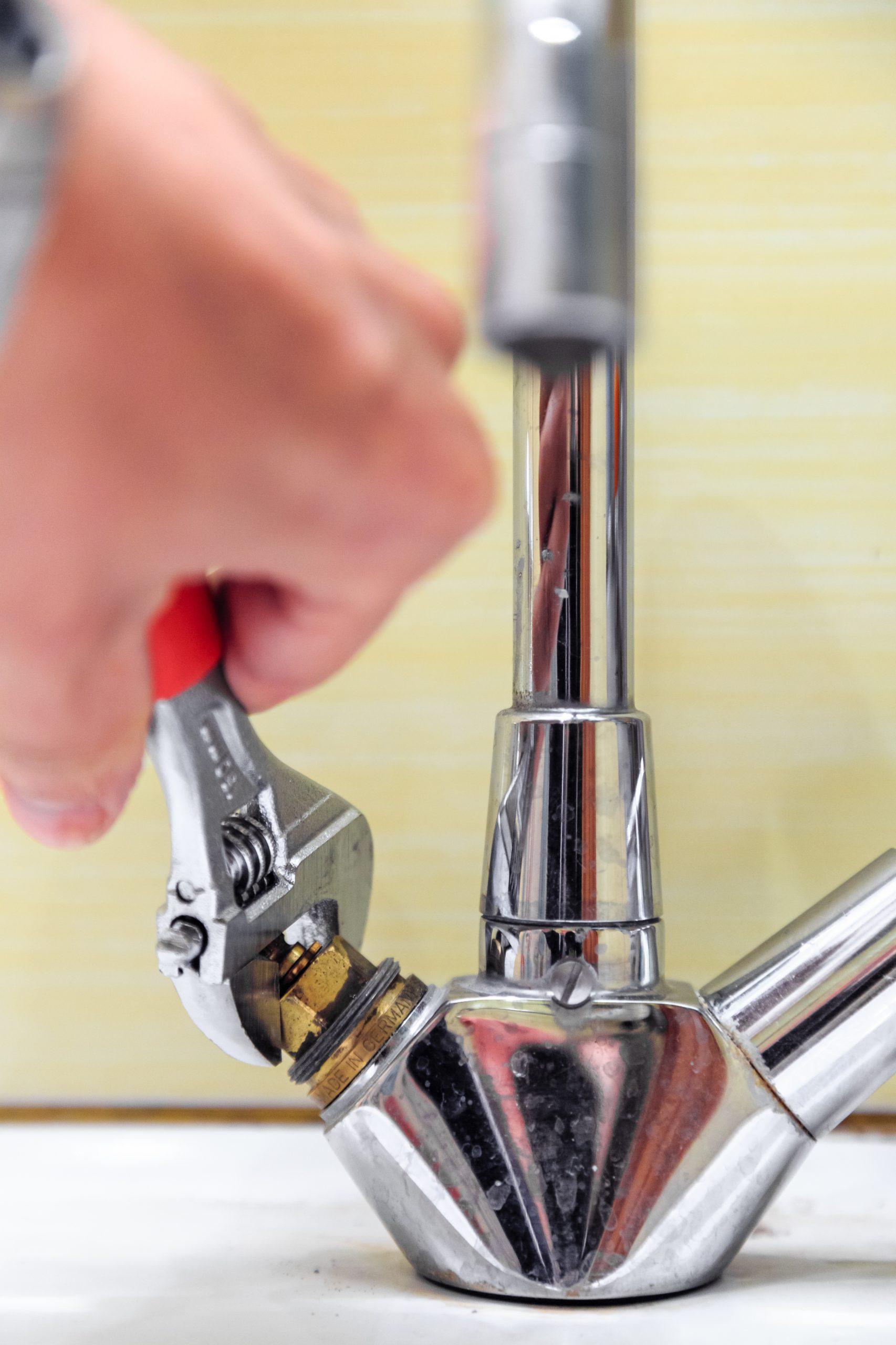 plumber tightening a sink tap